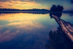 Vintage photo of beautiful sunrise over calm lake. Stock Image