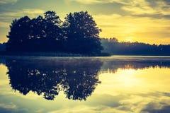 Vintage photo of beautiful sunrise over calm lake. Stock Photo