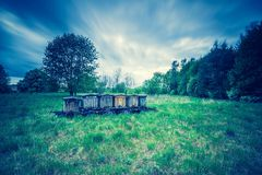 Vintage photo of bee hives on trail in rural landscape Royalty Free Stock Photography