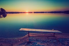 Vintage photo of bench on lake shore at sunset Royalty Free Stock Photo