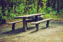Vintage photo of bench and table in forest. Place for resting for tourists. Stock Photography