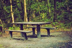 Vintage photo of bench and table in forest. Place for resting for tourists. Royalty Free Stock Image