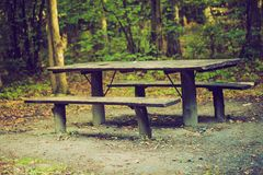 Vintage photo of bench and table in forest. Place for resting for tourists. Royalty Free Stock Images