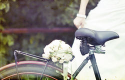 Vintage photo of bride and wedding bouquet on a bicycle Royalty Free Stock Photography