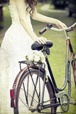 Vintage photo of bride and wedding bouquet on a bicycle Royalty Free Stock Photos