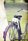Vintage photo of bride and wedding bouquet on a bicycle Royalty Free Stock Images