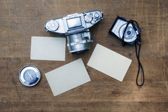 Vintage photo camera with blank photo frame on a wooden table Stock Photo