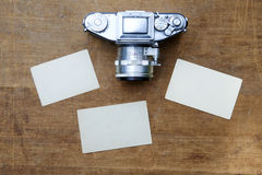 Vintage photo camera with blank photo frame on a wooden table Royalty Free Stock Images