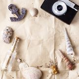 Vintage photo camera on craft paper with sand and sea shells mock up Stock Photos