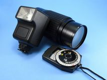 A vintage photo camera flash, a zoom camera lens and a photometer stock image