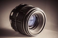 Vintage photo camera lens close up isolated on sepia background Royalty Free Stock Photography
