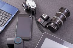Vintage photo camera next to a laptop a tablet and a smartphone royalty free stock image