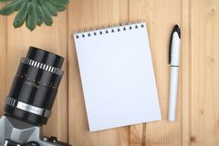 Vintage photo camera and notepad for typing. royalty free stock image