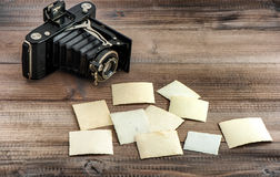 Vintage photo camera and old paper photos Royalty Free Stock Images