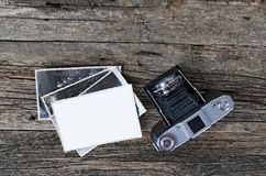 Vintage photo camera and photos. Old camera and black & white photographs on wooden background. Place for your photo on white paper and copy space on wood Stock Images