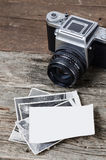 Vintage photo camera and photos. Old camera and black & white photographs on wooden background. Place for your photo or copy space on blank white paper Stock Photo