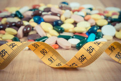Vintage photo, Centimeter and colorful medical pills and capsules, health care and slimming concept Royalty Free Stock Images