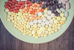 Vintage photo, Colorful medical pills, tablets and capsules on plate, health care concept Royalty Free Stock Photos