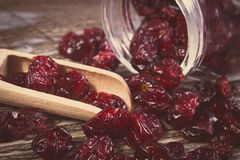 Vintage photo, Cranberries spilling out of glass jar on wooden table Royalty Free Stock Photography