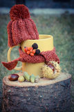 Vintage photo, Cup of beverage with woolen cap wrapped scarf on wooden stump Royalty Free Stock Image
