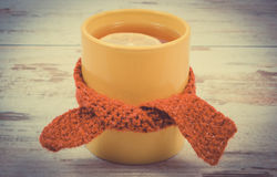 Vintage photo, Cup of hot tea with lemon wrapped woolen scarf Royalty Free Stock Photo