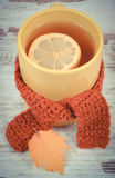 Vintage photo, Cup of tea with lemon wrapped woolen scarf and autumnal leaf Royalty Free Stock Images
