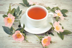 Vintage photo, Cup of tea and wild rose flower on old rustic wooden background Stock Photography