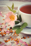 Vintage photo, Cup of tea with wild rose flower on old rustic wooden background Stock Photography