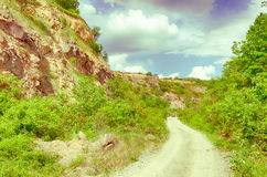 Vintage photo. Dirt road on the Tokaj Hill in Hungary. Hungarian countryside. Cloudy blue sky. Trees and rocks. Stock Photos