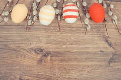 Vintage photo, Easter catkins and eggs wrapped woolen string on rustic board, festive decoration, copy space for text. Vintage photo, Easter catkins and eggs royalty free stock photography
