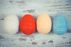 Vintage photo, Easter eggs wrapped woolen string on wooden background, decoration for Easter Stock Image