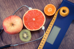 Vintage photo, Electronic bathroom scale, centimeter and fresh fruits with stethoscope, slimming and healthy lifestyles Royalty Free Stock Photo