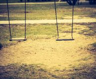 Vintage photo of empty swing on children playground Stock Photography