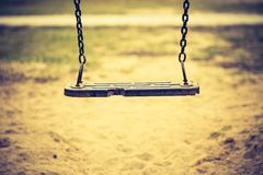 Vintage photo of empty swing on children playground Royalty Free Stock Image