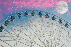 Vintage photo with ferris wheel. Against the moon colorful sky royalty free stock photography