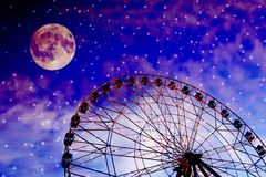 Vintage photo with ferris wheel. Against the moon colorful sky stock photography