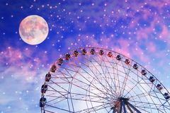 Vintage photo with ferris wheel. Against the moon colorful sky royalty free stock photos