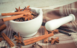 Vintage photo, Fragrant cloves and anise in mortar and spices on rustic board Royalty Free Stock Photos