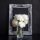 Vintage photo frame and flowers on a black textured background. Place for your text. Vintage photo frame and flowers on a black textured background Stock Image