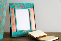 Vintage photo frame on wooden table over white wall background Stock Image