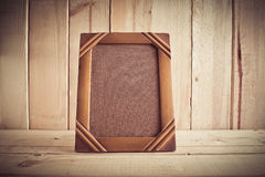 Vintage photo frame on wooden table over wood background Stock Photos