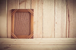 Vintage photo frame on wooden table over wood background Royalty Free Stock Photography