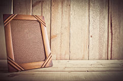 Vintage photo frame on wooden table over wood background Royalty Free Stock Image