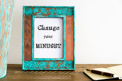 Vintage photo frame on wooden table with text CHANGE YOUR MINDSET Stock Photos