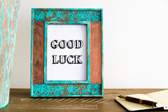 Vintage photo frame on wooden table with text GOOD LUCK Royalty Free Stock Photos