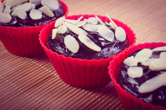 Vintage photo, Fresh baked chocolate muffins with sliced almonds Royalty Free Stock Image