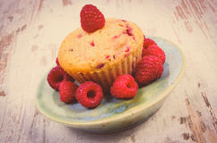 Vintage photo, Fresh baked cupcake with raspberries and fruits on old wooden background, delicious dessert Stock Photo