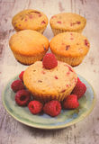 Vintage photo, Fresh baked cupcake with raspberries and fruits on old wooden background, delicious dessert Royalty Free Stock Photography