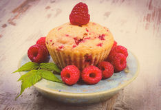 Vintage photo, Fresh baked cupcake and raspberries on plate on old wooden background, delicious dessert Stock Image