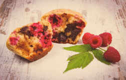 Vintage photo, Fresh baked muffins with chocolate and raspberries on wooden background, delicious dessert Royalty Free Stock Photos